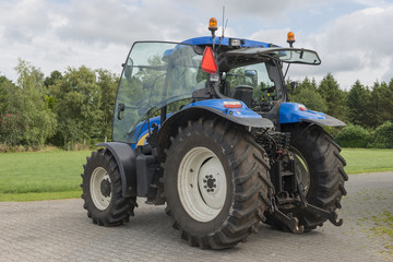 Modern blue tractor on a farmyard.