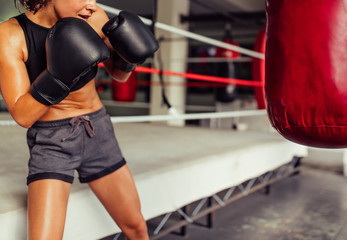 Muscular young woman practices on red punching bag