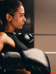 Female boxer leaning against ropes in boxing ring