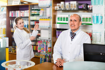 Professional pharmaceutists at reception of drugstore