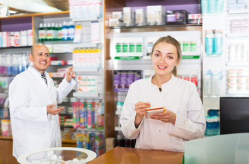 Young pharmacist and pharmacy assistant helping