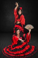 Two mature women posing in flamenco gowns