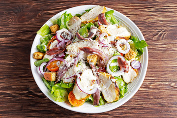 Ceasar salad with grilled chicken fillets, red onion rings, lettuce, orange cherry tomatoes, croutons, grated parmesan cheese, seasoned  anchovy