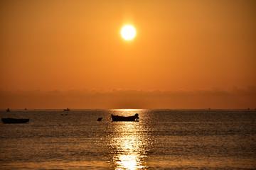 Alba con sole rosso e silhouette di barca