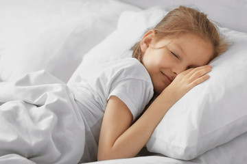 Cute sleeping girl in white bed
