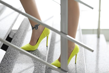 Woman with tattoo on her leg in high heeled shoes on the stairs