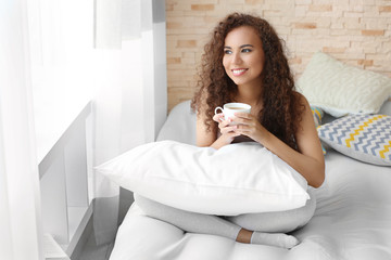 African American woman with a cup of coffee on bed