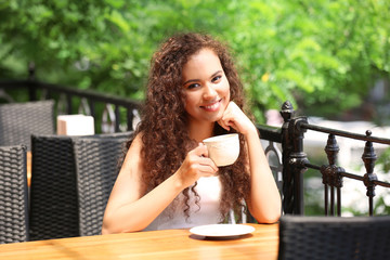African American woman with a cup of coffee in cafe