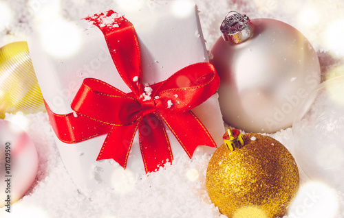 white decorative christmas gift box with ribbon and balls on snow view from above
