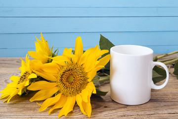 White coffee mug with sunflowers on a blue background.
