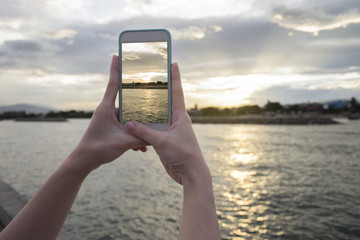 Close up of woman's hand holding smart phone, mobile, smart phone over blurred beautiful sea with sunset moment to take a photo of the sea,selective focus,filtered image