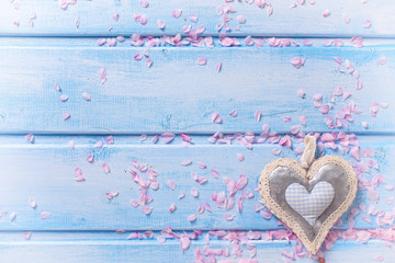 Background  with  decorative heart  and pink petals on blue wood
