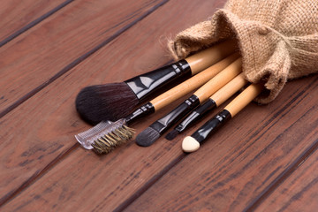 set of brushes for makeup scattered chaotically on wooden backgr