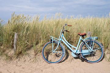 blaues Fahrrad abgestellt in den niederländischen Dünen
