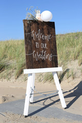 easel with wooden WELCOME TO OUR WEDDING sign in front of dunes