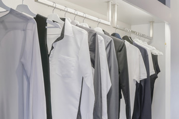 Row of men's shirt hanging in wardrobe