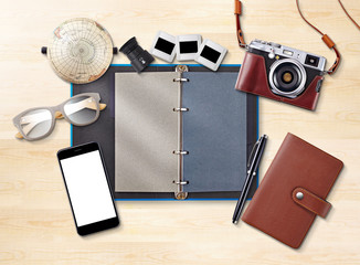 Notebook or Diary and accessories on wooden table,vintage camera ,smart phone, topview