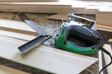 Fretsaw, metal ruller and tongue and groove boards on working pl