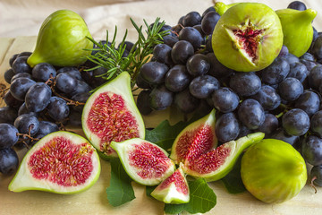 Still life of fresh colorful fruits. Bunch of black grapes, gree