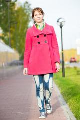 Beautiful woman in red coat walking autumn street. Girl walking on a beautiful fall day.
