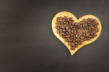 Sales of coffee. Coffee beans on wooden background.
