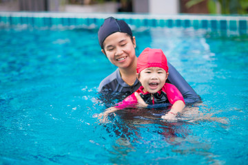 Young active mother having fun in a swimming pool with asian kid