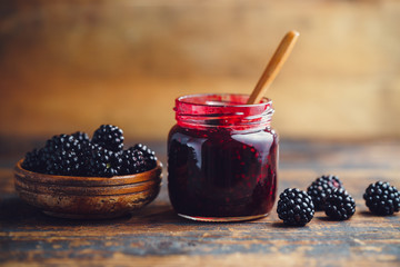 Fresh homemade blackberry jam in glass jar on a wooden background