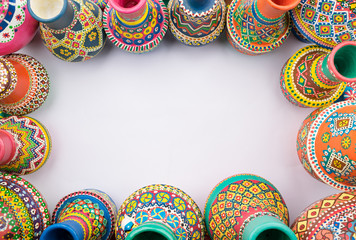 Frame of painted colorful pottery vases on white background