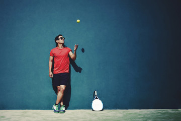 Sportsman tossing a tennis ball while taking break after paddle game