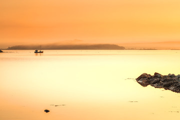 Lonely boat in distance from sea shore. Early morning time, sunrise scene.