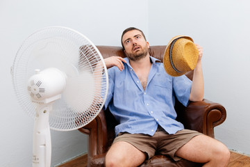 Flushed man feeling hot in front of a fan Wall mural