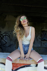 Sexy young girl in mirrored sunglasses posing on window sill