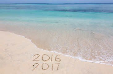 Years 2016 and 2017 are inscribed on sandy beach