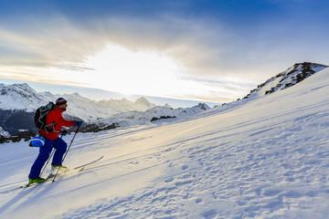 Ski tour - skier climbing to the top