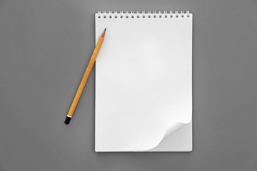 Blank notebook and pencil on grey background