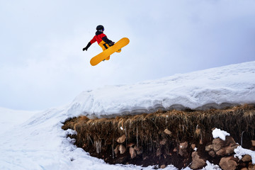 Snowboarder jumping from   springboard on a snowy hill with grass.