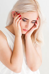 Strong migraine concept. Poor beautiful blonde woman with severe headache, close-up on white background
