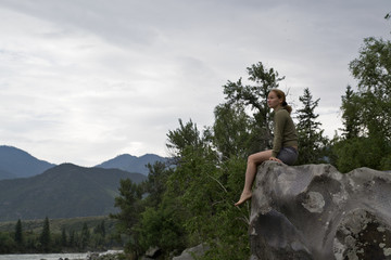young woman sitting on the edge of the cliff above the mountain river