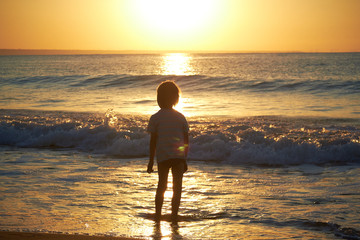 boy playing on the beach at sunset