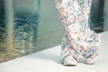 Close up image of girl wearing floral pants and white sneakers next to the swimming pool