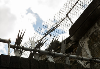 close up of fence with barbed wire and mesh