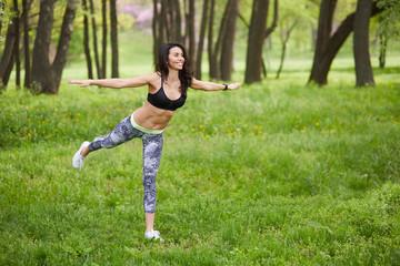 Young woman balances on one leg.