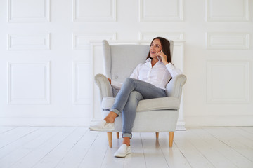 Female talking on the smart phone while sitting in an armchair