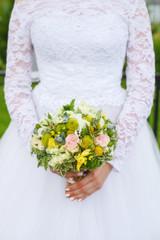 Beautiful green wedding bouquet in bride's hands, closeup