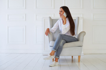 Good looking female in casual outfit speaking on smartphone sitt