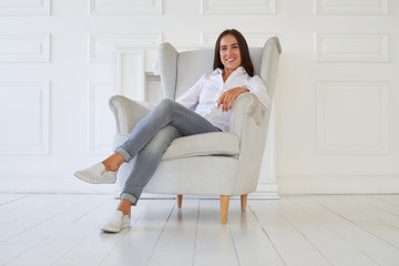 Peace of minds of young happy woman while sitting in an armchair