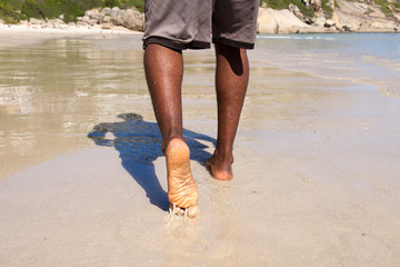 Man walking with bare feet on the beach