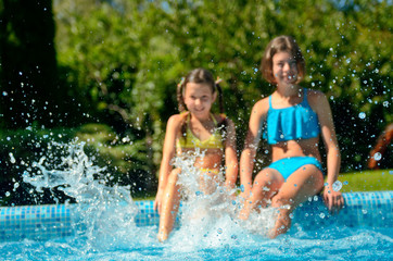 Kids in swimming pool have fun and splash in water, children on family vacation