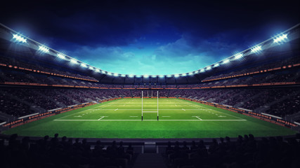 illuminated rugby stadium with spectators and green grass