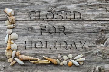 """written engraved on wooden table """"closed for vacation"""" with the shells"""